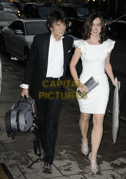 Ronnie Wood & guest.The Marie Curie Cancer Care fundraising dinner, The Claridge's Hotel,  London, England..May 15th, 2012.full length black suit white shirt dress guitar case silver clutch bag.CAP/CAN.©Can Nguyen/Capital Pictures.
