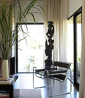 In the living room a classic chrome-and-leather Wassily chair by Marcel Breuer is juxtaposed with a contemporary sculpture in front of a large picture window