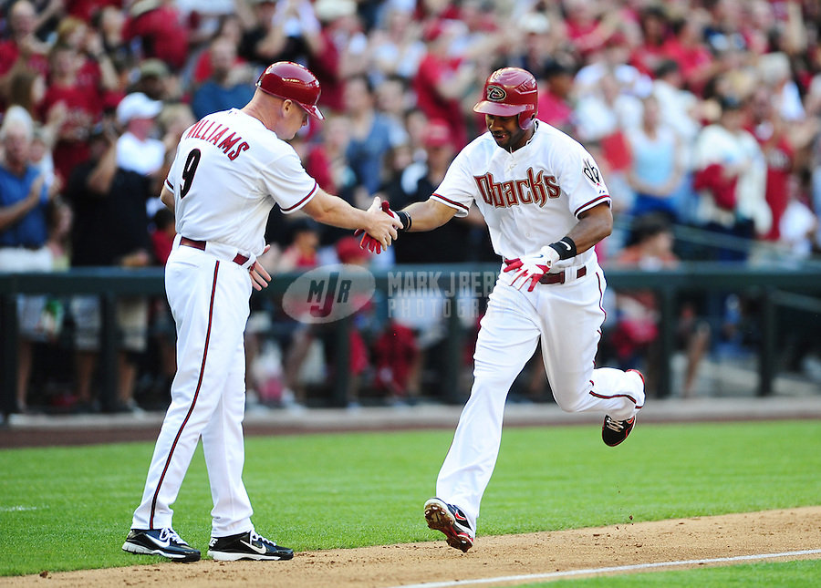 Apr. 6, 2012; Phoenix, AZ, USA; Arizona Diamondbacks outfielder Chris Young (right) is congratulated by third base coach Matt Williams after hitting a two run home run in the first inning against the San Francisco Giants during opening day at Chase Field.  Mandatory Credit: Mark J. Rebilas-