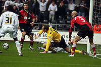 Pictured: Mark Schwarzer (C) goalkeeper of Fulham manages to scoop up the ball from a close encounter with Mark Gower of Swansea (not pictured)<br />