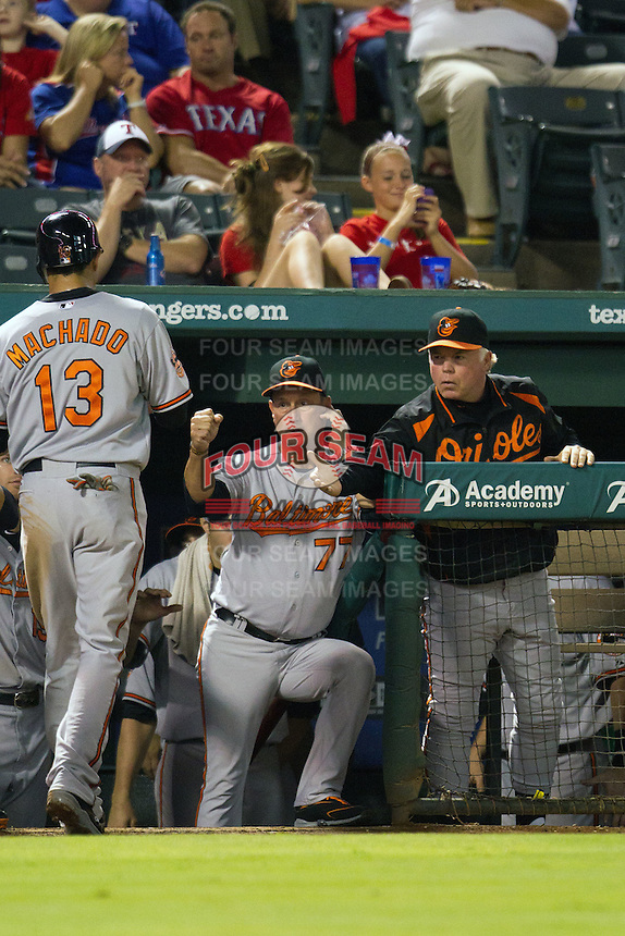 Baltimore Orioles manager Buck Showalter greets Manny Machado #13 in the dugout during the Major League Baseball game against the Texas Rangers on August 21st, 2012 at the Rangers Ballpark in Arlington, Texas. The Orioles defeated the Rangers 5-3. (Andrew Woolley/Four Seam Images).