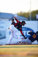 Batavia Muckdogs shortstop Garvis Lara (34) tags out Tommy Edman (16) sliding into second during a game against the State College Spikes on June 23, 2016 at Dwyer Stadium in Batavia, New York.  State College defeated Batavia 8-4.  (Mike Janes/Four Seam Images)