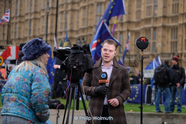 Press TV news presenter on College Green, outside the Houses of Parliament, on the day MPs voted decisively to reject Theresa May's withdrawal deal with the EU.  Westminster, London..
