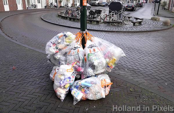 Nederland - Gouda - December 2018.  Gescheiden afval. Plastic zakken met afval hangen aan een paal. Inzameldag.   Foto Berlinda van Dam / Hollandse Hoogte
