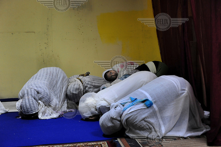 A girl lays on her mother's back as Eritrean women conduct a prayer at their makeshift church. Eritreans are the largest community of asylum seekers arriving in Israel since 2006.
