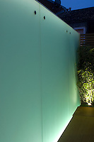 Sand blasted glass panel wall provides simple and effective additional night light to the garden