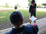 Vern Moehrs (left), longtime manager of the Waterloo Millers men's baseball team, hands the lineup to Waterloo player Jeremy Rettig to walk it over to the scorer's table at the 48th Annual Valmeyer Mid-Summer Baseball Classic Tournament in Valmeyer, IL on July 4, 2019. <br /> Photo by Tim Vizer