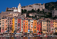 Portovenere, Italy. View of colorful waterfront buildings with cafes, laundry out the windows, and boats in the harbor.