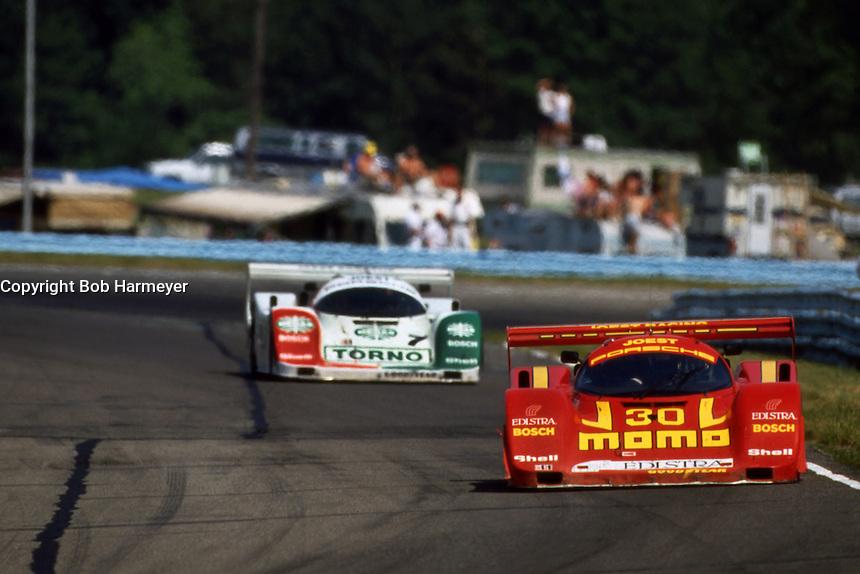 WATKINS GLEN, NY - JUNE 28: The Joest Racing Porsche 962C of Gianpiero Moretti and John Paul, Jr., leads the Joest Racing Porsche 962C of Oscar Larrauri and John Winter during the Camel Continental IX IMSA GTP/Lights race at the Watkins Glen International track near Watkins Glen, New York, on June 28, 1992.
