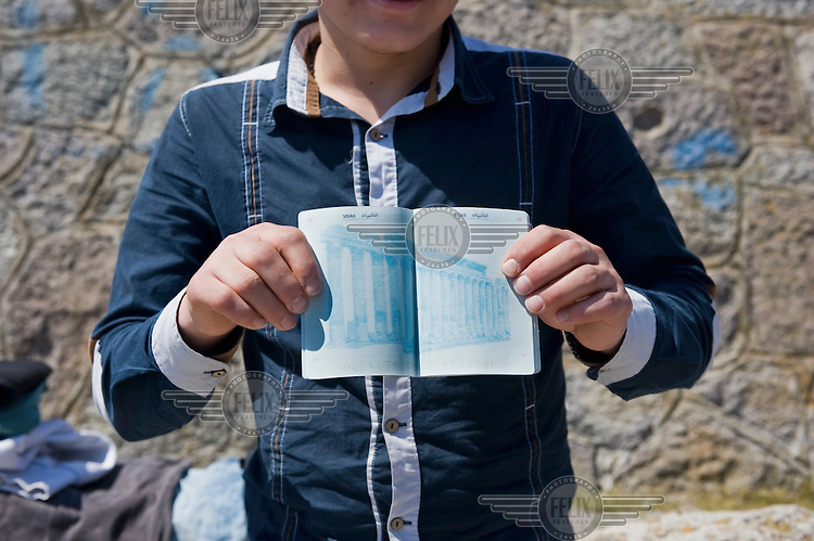 An 18 year old Syrian refugee shows his unstamped passport in the port of Molyvos, Lesbos island, hours after his boat was rescued by the Greek Coast Guard. Everyday hundreds of refugees, mainly from Syria and Afghanistan, are crossing in small overcrowded inflatable boats the 6 mile channel from the Turkish coast to the island of Lesbos in Greece.