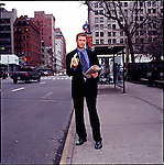 Man in suit standing on sidewalk holding a newspaper and a banana