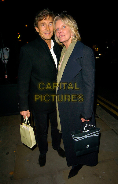 NIGEL HAVERS & GUEST.La Brasserie relaunch party, Brompton Road, London, England..November 13th, 2007.full length black blue coat goody bag .CAP/CAN.©Can Nguyen/Capital Pictures
