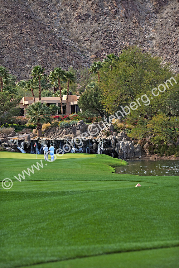 Golf players in front of waterfall