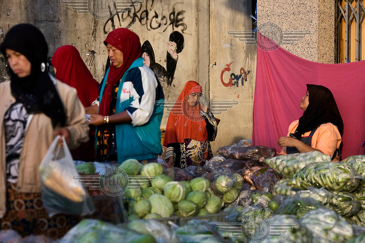 Women buy fruit and vegetables from the market in Pattani.