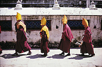There are quite a lot of Tibetans resident in Nepal and several temples and monasteries where they have settled. Here, some apprentice Tibetan yellow hat monks process in front of the Bodhnath Stupa in Kathmandu.