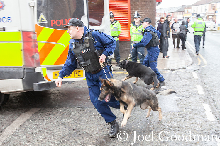 © Joel Goodman - 07973 332324 . 03/03/2012 . Heywood , UK . Police with dogs chase after demonstrators as they disperse in Heywood town centre after the National Front hold a rally in protest against an alleged paedophile ring that had been operating in the area . There is currently (3rd March 2012) a case being tried at Liverpool Crown Court in relation to the allegations . Last Thursday (23rd February 2012) a protest organised in the town in relation to the same story resulted in Asian business being attacked by an angry mob . Photo credit : Joel Goodman