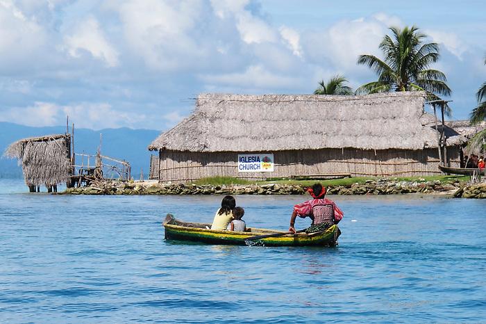 Indígenas guna / indígena remando hacia la iglesia en la comarca de Guna Yala, Panamá.