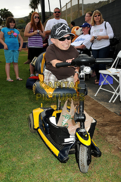 VERNE TROYER .Steve Garvey's Celebrity Softball Game for ALS Research held at Pepperdine University's Eddy D. Field Stadium, Malibu, California, USA..July 10th, 2010.full length brown shirt check short sunglasses shades baseball cap hat wheelchair DUB edition scooter electric sitting riding driving.CAP/ADM/BP.©Byron Purvis/AdMedia/Capital Pictures.