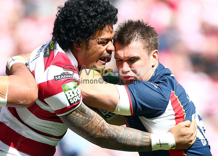 PICTURE BY VAUGHN RIDLEY/SWPIX.COM - Rugby League - Challenge Cup Quarter-Finals - Wigan Warriors v St Helens Saints - DW Stadium, Wigan, England - 12/05/12 - St Helens Paul Clough is tackled by Wigan's Epalahame Lauaki.