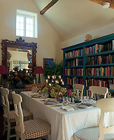 The dining room also doubles as a library with an entire wall lined with bookshelves