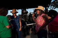 Wellsville, Kansas, May 28, 2011 -  Fourth generation family farmer Robin Dunn  (in cut off denim shirt) talks with friends during the annual Cottonwood Mini Masters, an event hosted by Cottonwood Inc. which provides services for mentally and physically challenged adults. Dunn provides wagon rides for the event every year. ..Dunn bought her great grandparents homestead from her father in 1993, and today grows soybeans, corn, sorghum and hay, and maintains a small herd of Black Angus cattle and eight horses which she uses to for wagon and stage coach rides.  According to the most recent Department of Agriculture data, there are more than 306,000 farms run primarily by women in 2007, representing about 14 percent out of the 3.3 million American farms.  That's up from 237,819 or 11 percent in 2002, and a big increase from the 1980s when about five percent of U.S. farms were operated by women. Dunn has branched out from her farming business, using her century-old dairy barn to host 25 to 30 weddings and other events a year. She also attracts tourists for farm tours and carriage rides, and holds sessions with school children to teach them about faming.