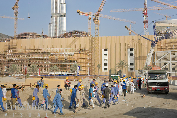 Foreign workers arriving by the busload to a mall construction site in Dubai