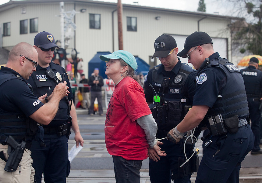 Bernadette Rodgers is arrested for taking part in a demonstration, blocking BNSF railroad tracks in Vancouver Saturday June 18 2016. (Photo by Natalie Behring for the Columbian)