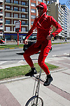 Montevideo, Uruguay - A Stret performer rides a unicycle on the sidewalk as part of a promotion for Claro Mobile phones