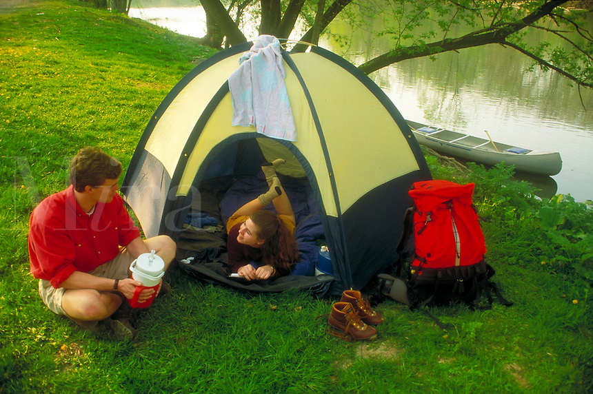 A college age male and female enjoy conversation at their tent along a river with canoe tied and backpack, shoes and other camping gear. Young couple male and female. Pennsylvania United States.