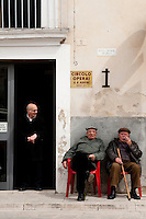 Locals relaxing in the piazza in the historic village of Ragusa, part of the Unesco World Heritage site of the Baroque Towns of the Val di Noto, Sicily, Italy