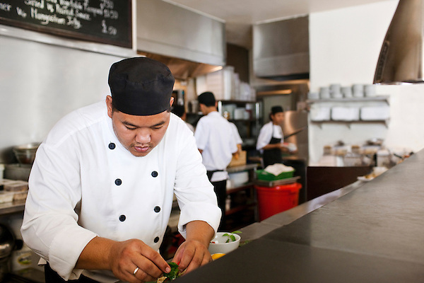 Chef preparing dish in the open kitchen of FCC Angkor Kitchen, Siem Reap, Cambodia.