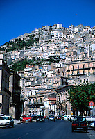 Houses rise up the mountain in Modica, Sicily