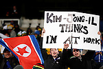 """15 JUN 2010: North Korea fans hold a sign reading, """"Kim-Jong-Il thinks I'm at work"""" in the stands, pregame. The Brazil National Team played the North Korea National Team at Ellis Park Stadium in Johannesburg, South Africa in a 2010 FIFA World Cup Group G match."""