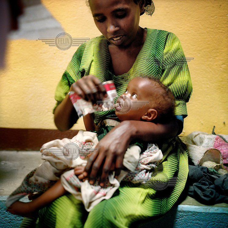 A woman feeding her baby with Plumpy'nut (Plumpy), a highly nutritious, peanut-based supplement that has a shelf life of 24 months, costs around US$0.06 per sachet and is used widely for famine relief.