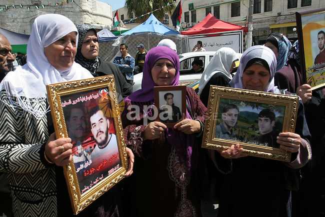 Palestinian women hold pictures of relatives during a protest calling for the release of Palestinian prisoners from Israeli jails, in the West Bank city of Nablus , Sunday, April 10, 2011. Israel currently holds about 8,000 Palestinian prisoners in its prisons. Photo by Wagdi Eshtayah