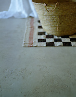 A detail of the pitted and mottled surface of the poured concrete floor in the master bedroom