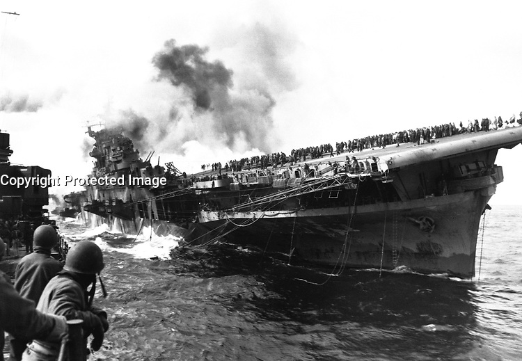 USS SANTA FE lays alongside of USS FRANKLIN rendering assistance after carrier had been hit and set afire by a Japanese dive bomber.  March 1945.  (Navy)<br /> Exact Date Shot Unknown<br /> NARA FILE #:  080-G-273880<br /> WAR &amp; CONFLICT BOOK #:  979