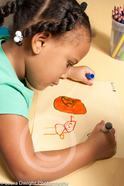 Education preschool 4 year olds art activity girl drawing recognizable human figures, using marker and drawing with right hand