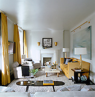 Yellow taffeta curtains and a yellow sofa by Steven Gambrel add warmth and depth to the living room