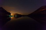 Franconia Notch State Park - Echo Lake at  night in the White Mountains, New Hampshire USA during the summer months. Artists Bluff is off in the distance and the reflection of the big dipper can be seen in the lake (foreground).