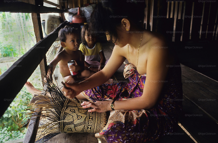 1991: Kenyah natives, women and children. She is weaving a traditional rattan sack from rainforest materials, on longhouse verandah. Long Geng, Belaga district, Sarawak, Borneo<br />