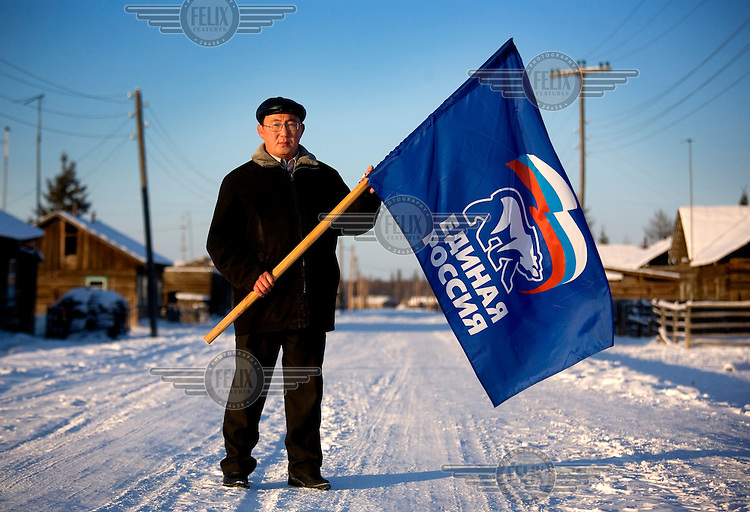 Nikifor Alfonski, head of the Bedime village in Yakutia, holds a United Russia flag, the party that supports Prime Minister Putin and President Medvedev.