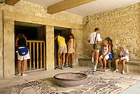 Tourists inspect a royal chamber below ground in the ancient Minoan palace at Knossos which contains a carved stone bowl and a carved stone throne (occupied by one of the tourists).