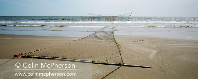 The beach at St. Cyrus, Aberdeenshire, with a 'jumper' net used for catching wild Atlantic salmon partially submerged in the North Sea. The once-thriving Scottish salmon netting industry fell into decline in the 1970s and 1980s when the numbers of fish caught reduced due to environmental and economic reasons. By 2007, only a handful of men still caught wild salmon and sea trout using traditional methods, mainly for export to the Continent.