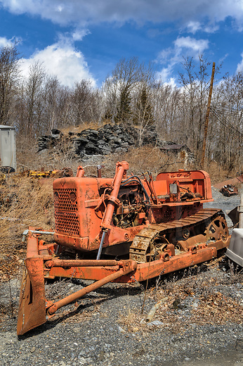 Abandoned bulldozer in Allis Chalmers orange sitting at an old mining site in Pennsylvania, PA, USA.