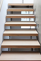 A modern staircase with wooden treads. Square low level lights are embedded in a concrete side panel.