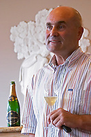 Serge Lefevre, president of Union Champagne, in front of a sculpture showing the grape harvest and holding a glass of de Saint Gall champagne, with a wine bottle in the background, the Union Champagne cooperative, also called Champagne de Saint Gall in Avize, Cote des Blancs, Champagne, Marne, Ardennes, France, low light grainy grain