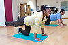 Young adults doing floor exercising in an aerobics class at their sports leisure centre,