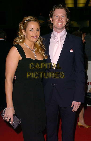 STEVE MCMANAMAN & PARTNER.Match Point UK Premiere Arrivals held at Curzon Mayfair Cinema, London..UK, United Kingdom..18th December 2005.Ref: CAN.half length with together navy blue suit white shirt tie black fitted dress curvy.www.capitalpictures.com.sales@capitalpictures.com.©Capital Pictures