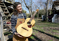 NWA Democrat-Gazette/DAVID GOTTSCHALK Aviva Steigmeyer, describes her guitar making process after playing one of her guitars Tuesday, March 26, 2019, at her Preservation Guitar Company in Fayetteville. Steigmeyer is also a member in the musical group The Ozark Highballers.